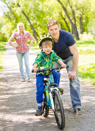 teaches: mother and father teaches his son to ride a bike