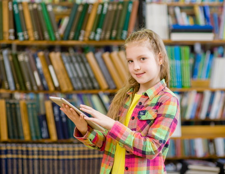 Teen  girl using a tablet computer in a library. photo