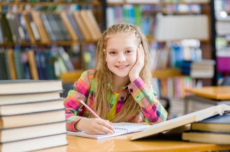 niños estudiando: Muchacha adolescente feliz estudiando en la biblioteca. Foto de archivo