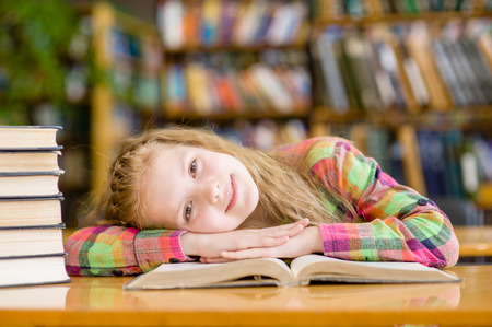 tutorials: Happy teen girl lying on table in library. Stock Photo
