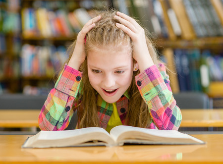 school kids: Surprised girl reading a book in the library.