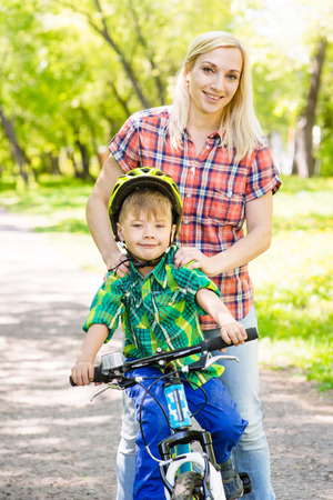 mom son: mom have fun with her son riding a bicycle in a park