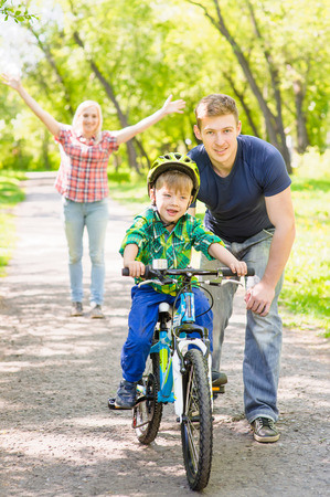 mother and children: mother and father teaches his son to ride a bike