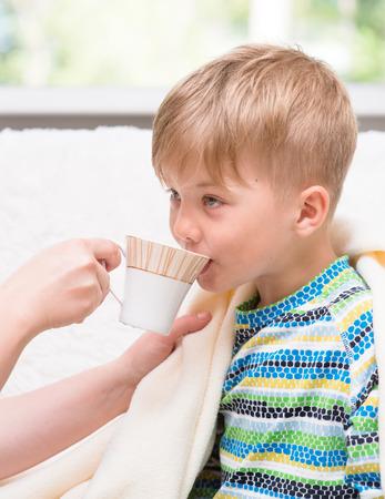 enfermos: madre da de beber al niño enfermo