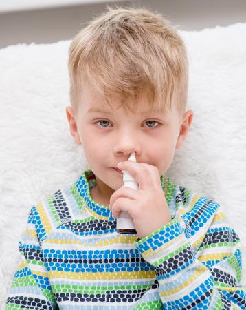 enfermo: Niño enfermo con la gripe usando aerosol nasal