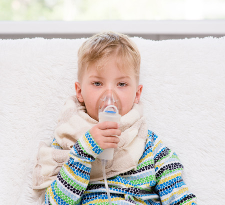 sick little boy makes inhalation home