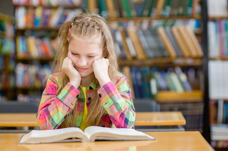 library: Muchacha triste leer un libro en la biblioteca.