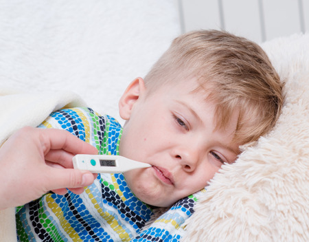 sick: Sick kid with high fever laying in bed and mother taking temperature.