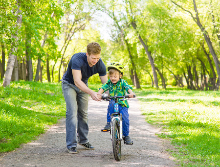 father teaches his son to ride a bike in park. Stock Photo