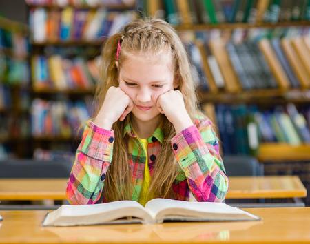 niños sentados: Muchacha triste leer un libro en la biblioteca.