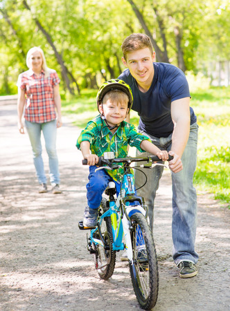 teaches: mother and father teaches his son to ride a bike.