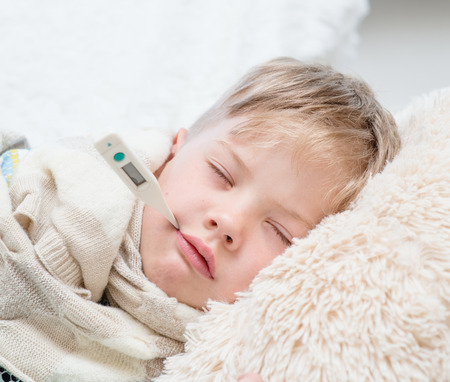 bebe enfermo: Dormir niño tendido en la cama con un termómetro en la boca. Foto de archivo
