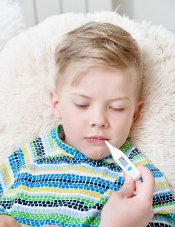 sick kid: Ni�o enfermo con fiebre alta que pone en la cama y la madre comprueba la temperatura.