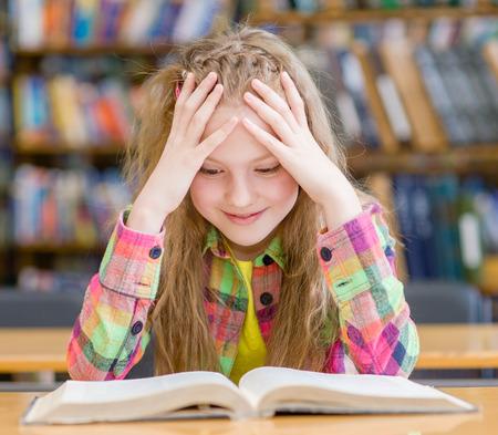biblioteca: Niña feliz leyendo un libro en la biblioteca.