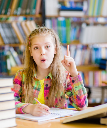 tutorials: young girl in the library showing finger up.