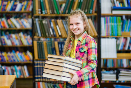 pile of books: Teen girl holding pile books in the library.