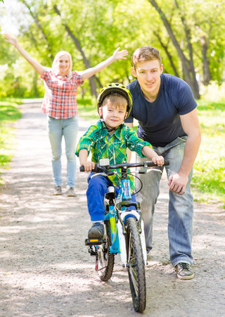teaches: father and mother teaches his son to ride a bike. Stock Photo