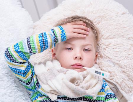 Muchacho enfermo triste con el termómetro por el que se en la cama.