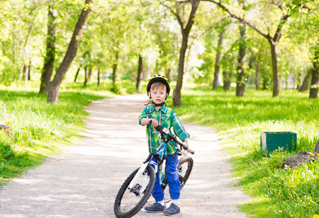 preschooler: child with a bicycle in a summer park. Stock Photo