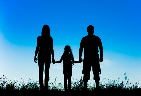 mum and daughter: silhouette father, mother and daughter holding hands at sunset. Stock Photo