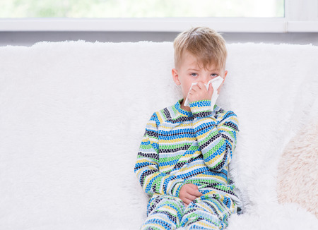 rheum: Little boy blowing his nose.