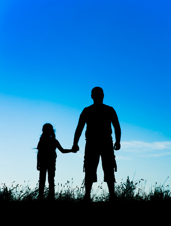 father daughter: silhouette father and daughter holding hands at sunset.