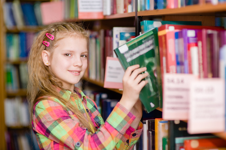 kid book: young girl chooses a book in the library.