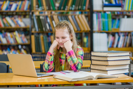 petite fille triste: sad teen girl in the library.