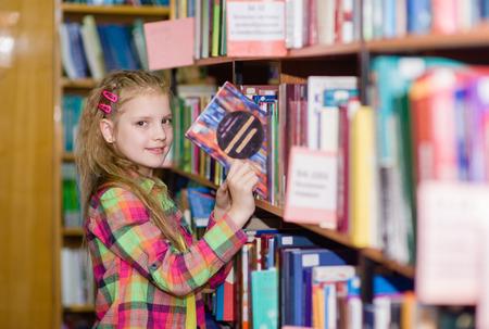 biblioteca: niña escoge un libro en la biblioteca.