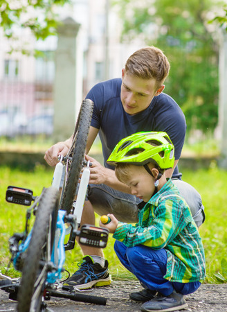 father helping his son fix bicycle. Stockfoto