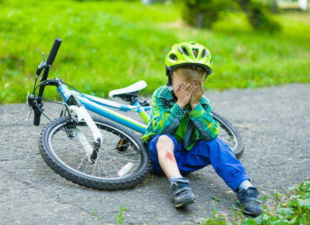 fell: boy fell from the bike in a park.