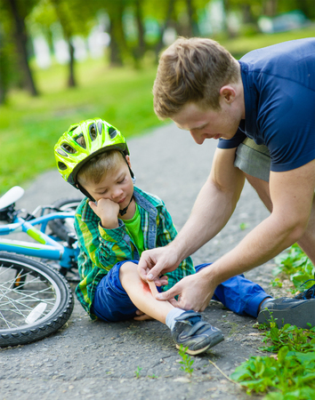 father putting aid on young boy\'s injury who fell off his bicycle.