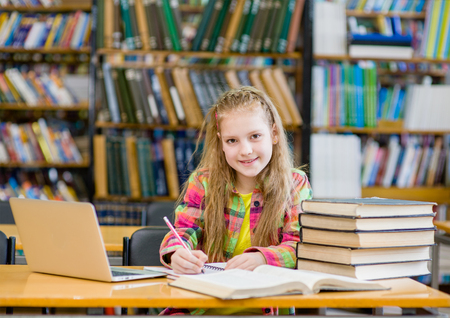 libraries: teen girl working in the library.