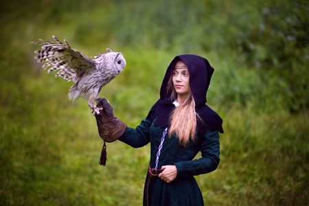 historical: girl in medieval dress is holding an owl on her arm. Stock Photo