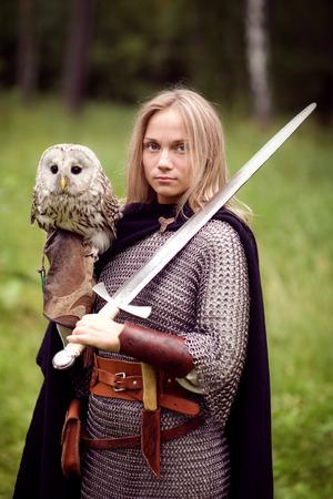 edad media: chica en una armadura y con una espada que sostiene una lechuza