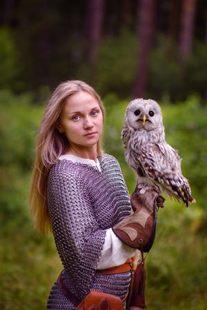 mail: girl in chain mail and with an owl in forest.
