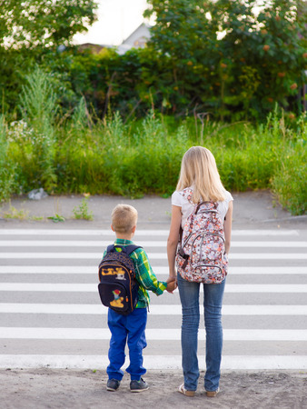 boy and girl crossing the road observing traffic rules.