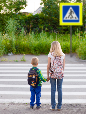 cross road: boy and girl want to cross the road at a pedestrian crossing.