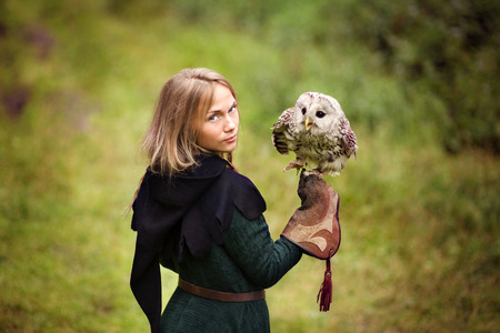 medieval: girl in medieval dress is holding an owl on her arm. Stock Photo