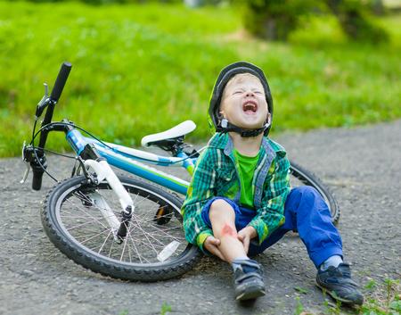 niños en bicicleta: muchacho cayó de la bicicleta en un parque. Foto de archivo