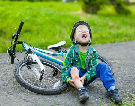 boy fell from the bike in a park.