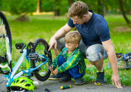 father and son: Father and son repairing bike together. Stock Photo