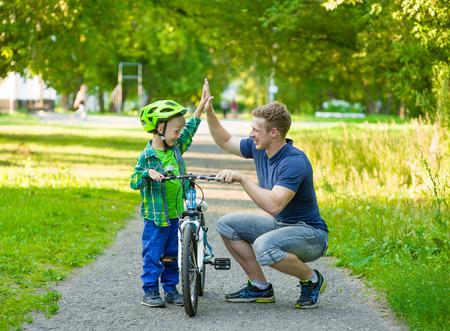 padres hablando con hijos: Padre e hijo dan de alta de cinco mientras que el ciclismo en el parque.