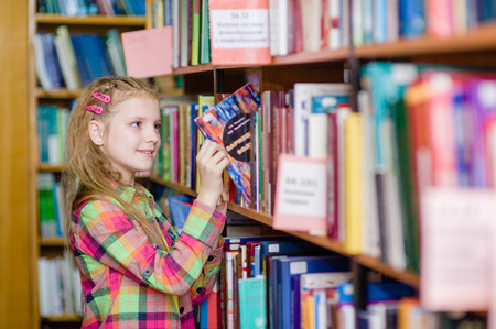 elementary school: young girl chooses a book in the library Stock Photo