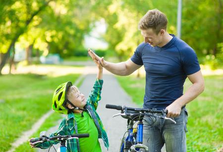 vader en zoon geven High Five tijdens het fietsen in het park