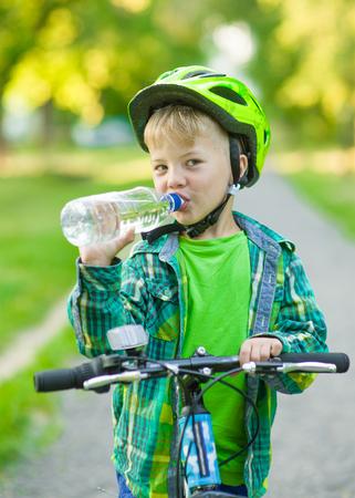 water sport: Little boy drinking water by the bike