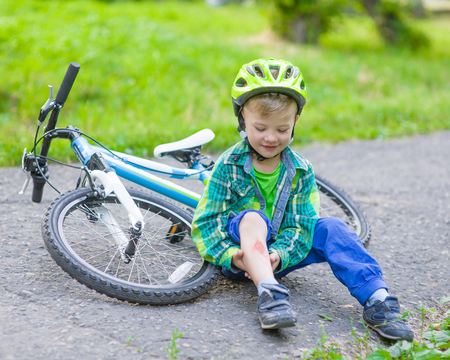 hurt: happy boy fell from the bike in a park