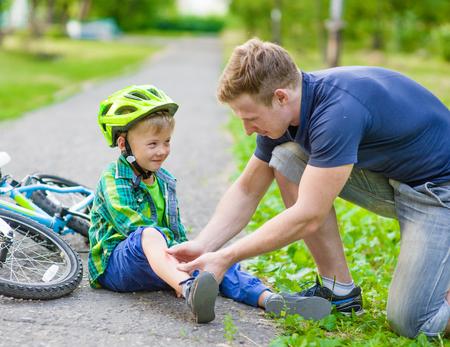 lesionado: padre poniendo una ayuda en la lesión de niño que se cayó de su bicicleta.