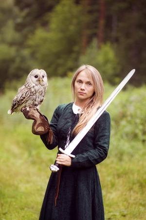 vestido medieval: chica en traje medieval es la celebraci�n de un b�ho en su brazo Foto de archivo