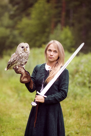 medieval dress: girl in medieval dress is holding an owl on her arm